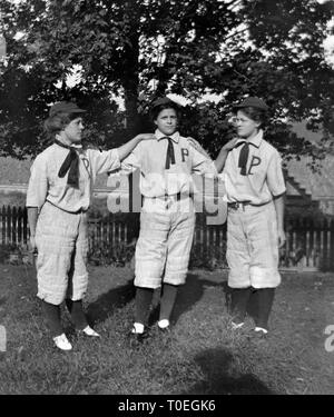 Three young women in baseball uniforms pose together in the backyard before the big game, ca. 1896. - Stock Image