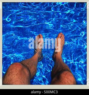 Man sitting on the edge of a swimming pool with legs in the water. - Stock Image