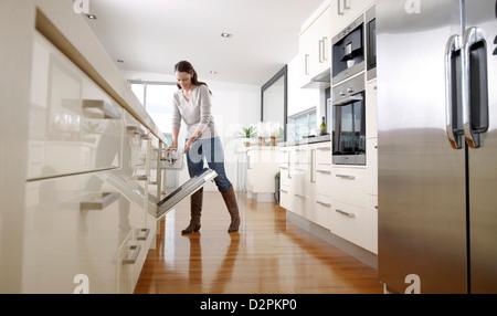 Woman loading a dish washing machine - Stock Image