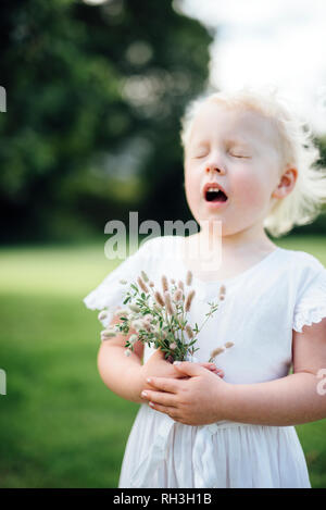 Girl with wildflowers sneezing - Stock Image