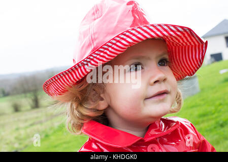 Little girl in wearing rain hat and raincoat - Stock Image