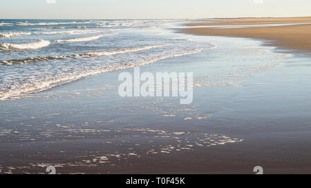 Shoreline with waves lapping the sand on a clear sunny day at Bamburgh, England UK. - Stock Image