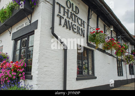 The Old Thatch Tavern public house with colourful hanging baskets in Stratford upon Avon - Stock Image