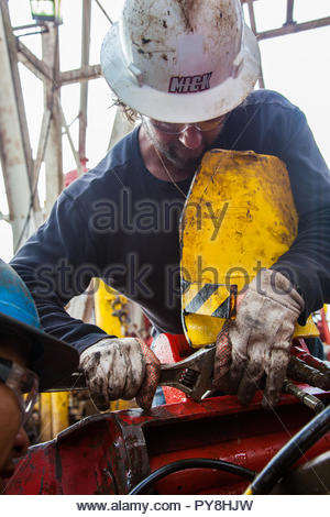 Worker using spanner on offshore oil platform - Stock Image