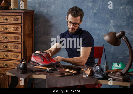 Portrait ofpleasant shoemakerlooking for any scratches on the footwear, close up photo - Stock Image