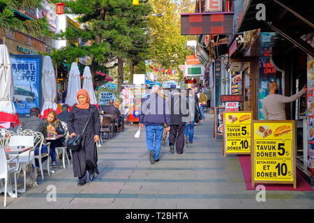 Pedestrian street filled with restaurant, with people eating outside even on a winter day.  Antalya, Turkey - Stock Image