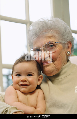 Portrait of 84 year old Italian American Grandmother holding '7month' old granddaughter - Stock Image