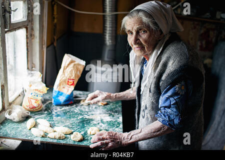 Old lady making pastries for her grandkids in her village kitchen. Ryazan Region. Russia - Stock Image