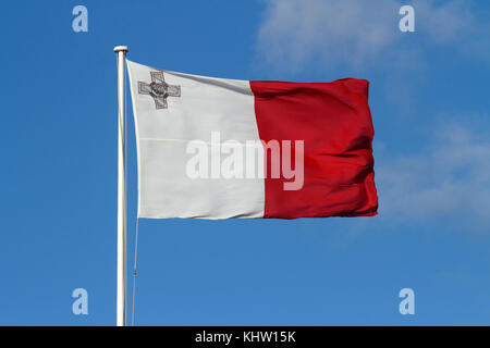 The national flag of Malta flying in a strong wind against a blue sky background. Maltese flag. - Stock Image