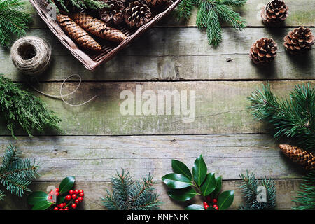 Christmas decoration using fresh and all natural materials on wooden table. - Stock Image