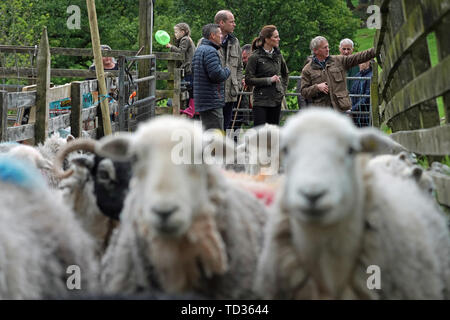 RETRANSMISSION ADDING NAMES The Duke and Duchess of Cambridge with Chris Brown (right) and Jimmy Brown (left) during a visit to Deepdale Hall Farm, a traditional fell sheep farm, in Patterdale, Cumbria. - Stock Image