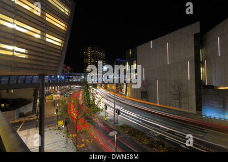 Light trails made by traffic passing through the built up area of the Cabot circus development in the city of Bristol at night. - Stock Image