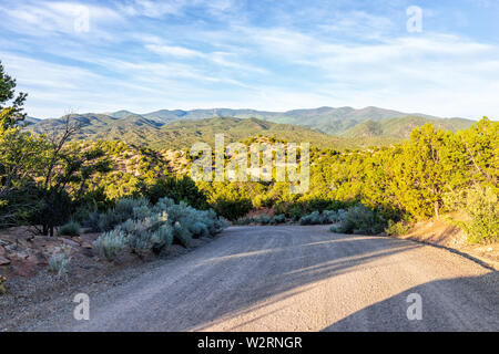Sunset Santa Fe, New Mexico mountains in Tesuque with golden hour light on green plants and dirt road to residential community - Stock Image