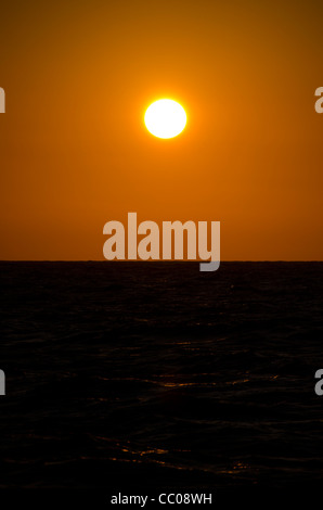 As the sun approaches the horizon over Australia's Great Barrier Reef it creates a rich, golden sky, with rays - Stock Image