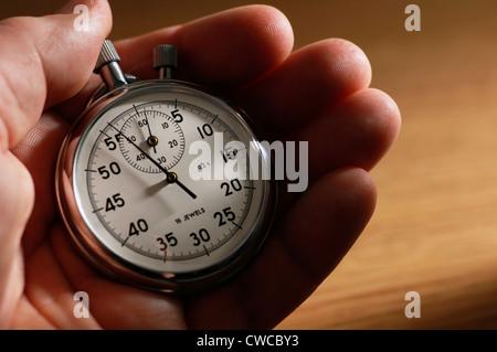 Man holding stopwatch - Stock Image
