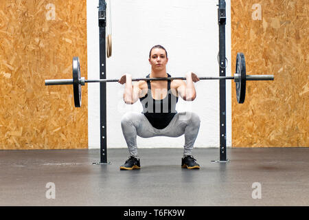Muscular young woman doing a front squat in a gym raising a barbell weight to her shoulders to strengthen her quads and glutes - Stock Image