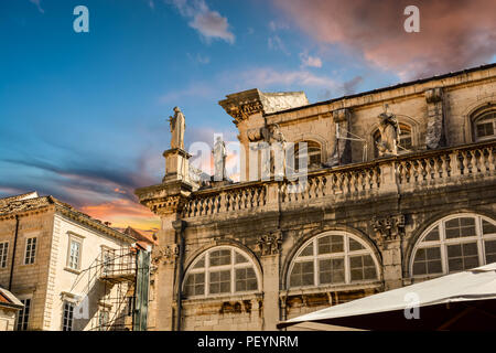 A colorful sky highlights statues on the roof of the Dubrovnik Cathedral of the Assumption of the Virgin Cathedral in Dubrovnik Croatia - Stock Image