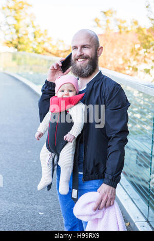 Father with baby girl in baby carrier - Stock Image