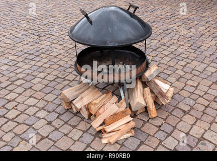 Unlit portable outdoor fire pit with kindling - Stock Image
