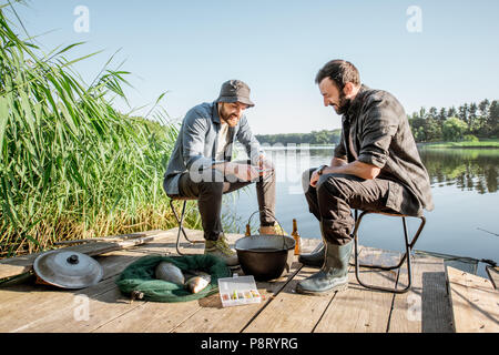 Two fishermen relaxing during the picnic on the wooden pier near the lake in the morning - Stock Image