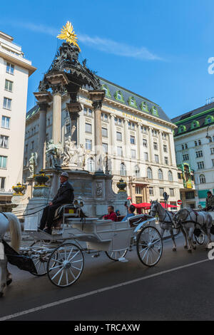 Vienna tourism, view of a horse drawn carriage containing tourists passing the Vermahlungsbrunnen monument in the Old Town area of Vienna, Austria. - Stock Image