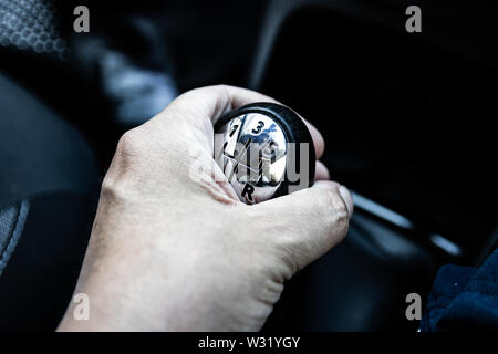 A hand on a car gear stick shifting gears - Stock Image