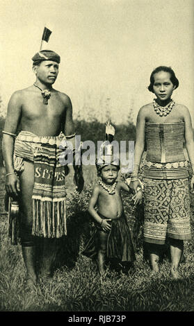 Sea Dayak (Dyak, Dayuh) or Iban family in traditional costume, Borneo, SE Asia (then part of the British Empire). - Stock Image