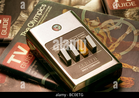 Zenith Space Command clicker remote placed on period-specific 1970's TV-guide magazines - Stock Image