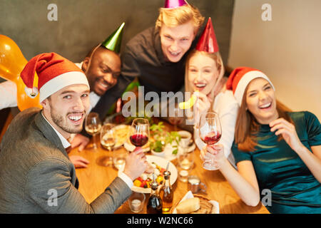 Young people at a Christmas party celebrate funny and happy with a lot of red wine - Stock Image