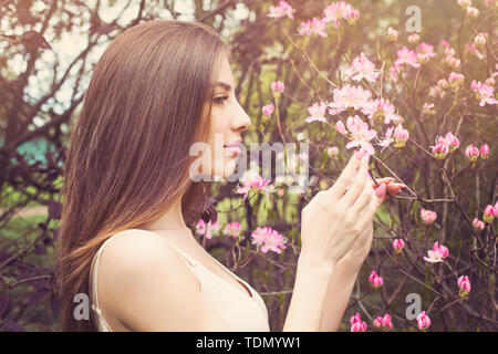 Beautiful woman face with clear skin, profile. Healthy girl sniffing flowers - Stock Image