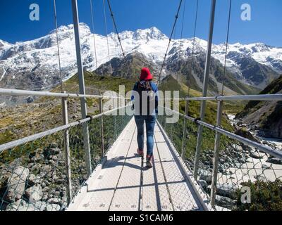 Female hiker walking on Suspension bridge at Mount Cook National Park in South Island New Zealand on a sunny day - Stock Image