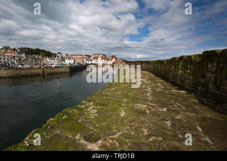 Village of Pittenweem, Scotland. Picturesque view of the southern breakwater of Pittenweem Harbour, with harbour houses at Gyles in the background. - Stock Image