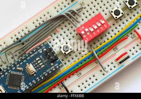 Electronics prototyping board (breadboard) with an Arduino Pro Mini clone and an assortment of switches and wires. - Stock Image