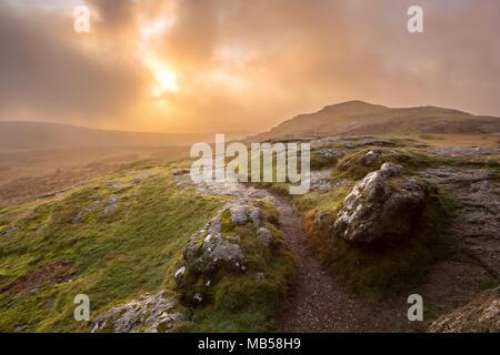 Dramatic sunrise on Saddle tor Dartmoor national park Devon Uk - Stock Image