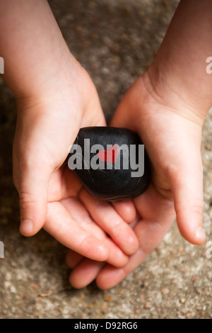 Child holding black rock with red heart painted on it - Stock Image