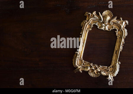 antiq golden photo frame in Rococo style, on dark rustic wooden background - Stock Image