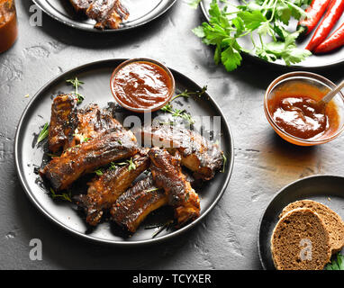 Spicy hot grilled spare ribs on plate over black stone background. Tasty bbq meat. - Stock Image