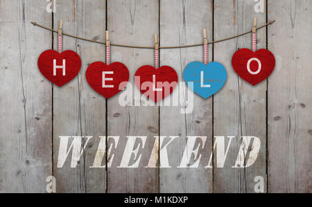 Hello weekend written on hanging red and blue wooden  hearts, on background of used weathered scaffolding wood - Stock Image