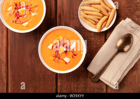 Salmorejo, Spanish cold tomato soup, shot from the top on a dark rustic wooden background with picos, typical breadsticks - Stock Image