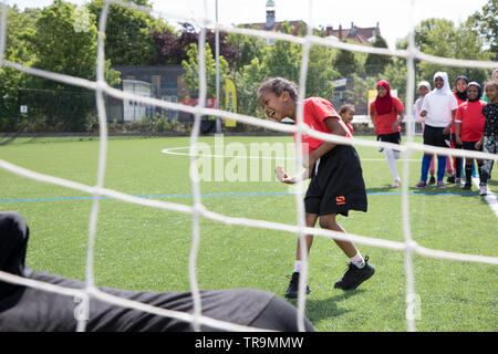 A young black girl takes a shot at goal during a training session on an astroturf pitch - Stock Image