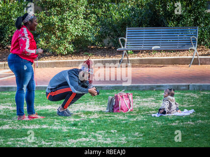 CHARLOTTE, NC, USA-1/8/19: A young black couple photographing infant in Romare Park in uptown.  Tight crop. - Stock Image