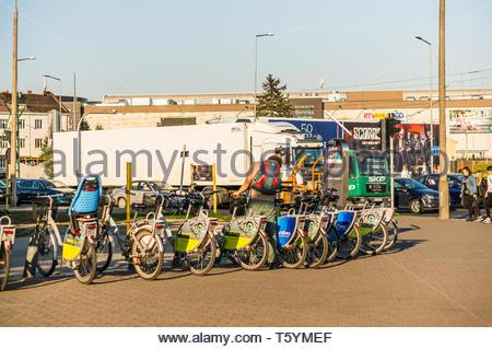 Poznan, Poland - April 18, 2019: Row of Nexbike rental bicycles close by a busy street at the Rataje roundabout. Man start to unlock a bike. - Stock Image