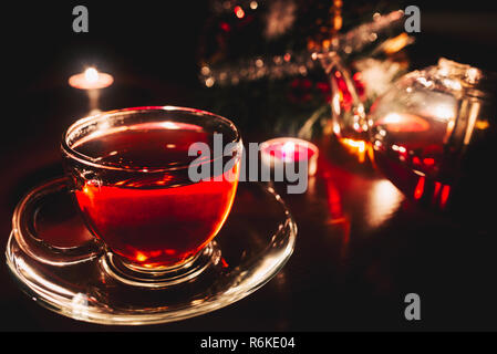 Cup of tea and kettle in dark room with candle lights - Stock Image