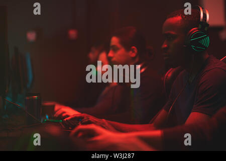 Group of concentrated multi-ethnic esport players sitting in front of computers in dark room full of red light and playing online games - Stock Image