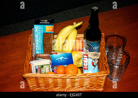 Welcome basket snack items fruit and big bottle beer - Stock Image