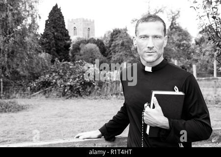 Good looking priest standing with one hard on gate while holding bible with orchard, field and church in background - Stock Image