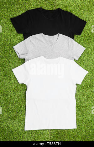 Stack of different coloured mens T-shirt on grass background. Vertical wiev. - Stock Image