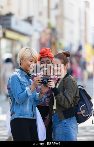 Young women friends using digital camera on urban street - Stock Image