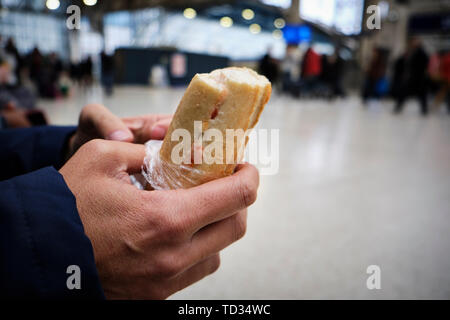 closeup of a caucasian man eating a sandwich in a train station or a tram station - Stock Image