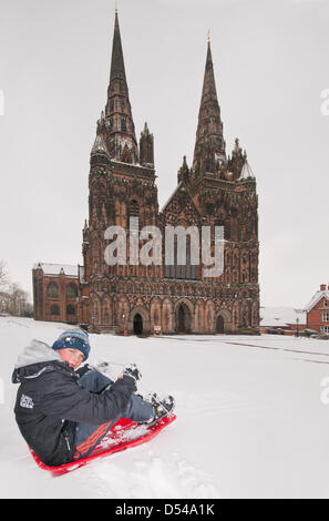 Lichfield Cathedral, Staffordshire, UK. 24th March, 2013. Young boy enjoying sledging in unseasonal snow in the - Stock Image
